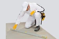 El trabajador controla niveles de cemento-base Imágenes de archivo libres de regalías