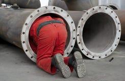 El trabajador controla un tubo de acero Foto de archivo libre de regalías