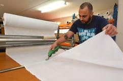 El trabajador cortó la nueva hoja de la tela para la nueva bandera nacional del nuevo Zea Foto de archivo