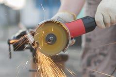 El trabajador corta el metal. Fotografía de archivo