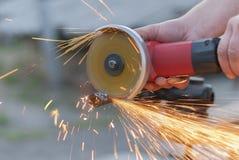 El trabajador corta el metal. Imagen de archivo