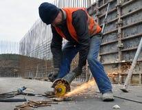 El trabajador corta la armadura del metal Fotografía de archivo