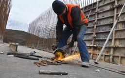 El trabajador corta la armadura del metal Foto de archivo