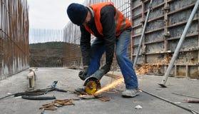 El trabajador corta la armadura del metal Imagen de archivo