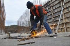 El trabajador corta la armadura del metal Fotos de archivo