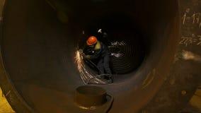 El trabajador corta el tubo del diámetro grande con la sierra circular metrajes