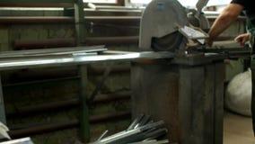 El trabajador corta un perfil del metal para una ventana del pvc en una sierra circular, una sierra de la circular y un perfil me metrajes