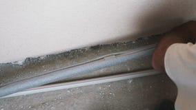 El trabajador cubre los tubos sanitarios con la capa del pvc El empalme de la tubería es cubierto con la capa por el trabajador d almacen de metraje de vídeo