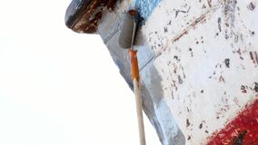 El trabajador cubre el metal con una pintura de la cartilla de la nave oxidada vieja en el astillero en puerto almacen de video