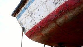 El trabajador cubre el metal con una pintura de la cartilla de la nave oxidada vieja en el astillero en puerto almacen de metraje de vídeo
