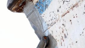 El trabajador cubre el metal con una pintura de la cartilla de la nave oxidada vieja en el astillero en puerto metrajes