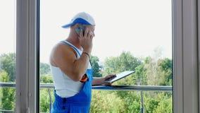 El trabajador de construcción atractivo está discutiendo algo en el teléfono, hace medidas de ventanas, hace notas adentro metrajes