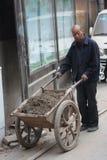 El trabajador de construcción chino lleva una carretilla con el suelo, hombre mayor, trabajo duro fotografía de archivo