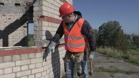 El trabajador de construcción con la almádena bate la pared de ladrillo almacen de video