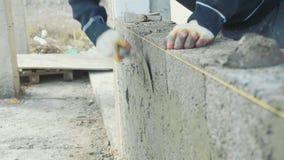 El trabajador de construcción construye la pared de ladrillo, opinión del primer en el emplazamiento de la obra almacen de video