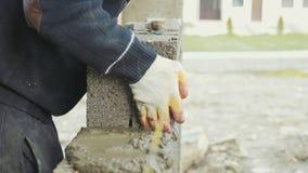 El trabajador de construcción construye la pared de ladrillo, opinión del primer en el emplazamiento de la obra almacen de metraje de vídeo