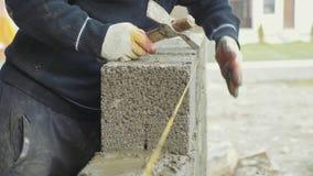 El trabajador de construcción construye la pared de ladrillo, opinión del primer en el emplazamiento de la obra metrajes