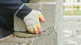 El trabajador de construcción construye la pared de ladrillo, opinión del primer en el emplazamiento de la obra imagen de archivo