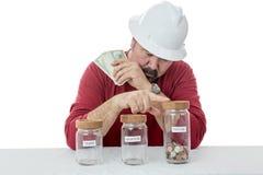 El trabajador de construcción decide sobre el uso del dinero Fotos de archivo libres de regalías