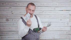 El trabajador de construcción del baile con el dinero y perfora adentro su mano almacen de video