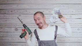 El trabajador de construcción del baile con el dinero y perfora adentro su mano almacen de metraje de vídeo