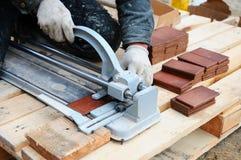 El trabajador de construcción del solador corta la teja de las tejas Trabajo con el equipo decorativo del corte de la teja en el  Imagen de archivo libre de regalías