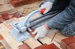 El trabajador de construcción del solador corta la teja de las tejas Trabajo con el equipo decorativo del corte de la teja en el  Imagenes de archivo