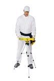 El trabajador de construcción en las batas blancas nivela la herramienta Fotografía de archivo