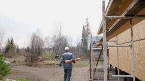 El trabajador de construcción en sitio lleva el tubo El constructor lleva juguetónamente un tubo de agua El trabajador lleva el t metrajes