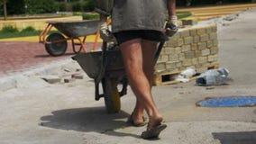 El trabajador de construcción está conduciendo una carretilla con las piedras de pavimentación en un emplazamiento de la obra almacen de metraje de vídeo