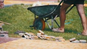 El trabajador de construcción está conduciendo una carretilla con las piedras de pavimentación en un emplazamiento de la obra Cám almacen de metraje de vídeo