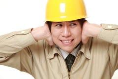El trabajador de construcción japonés sufre de ruido Imagen de archivo libre de regalías