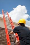 El trabajador de construcción sube la escala Foto de archivo