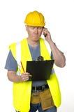El trabajador de construcción telefona y mira el sujetapapeles Foto de archivo