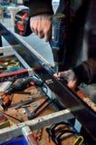 El trabajador de construcción Using Drill To instala la ventana Foto de archivo libre de regalías