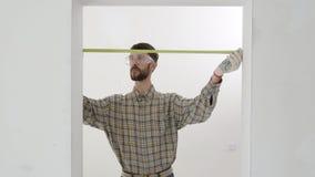 El trabajador de construcción utiliza cinta métrica almacen de metraje de vídeo