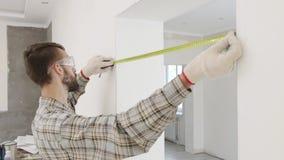 El trabajador de construcción utiliza cinta métrica almacen de video
