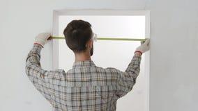 El trabajador de construcción utiliza cinta métrica metrajes