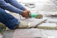 El trabajador de la amoladora corta una teja de piedra fotos de archivo