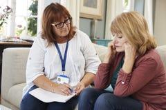 El trabajador de la ayuda visita a la mujer mayor que sufre con la depresión imagen de archivo libre de regalías