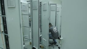 El trabajador de la cámara lenta conecta los alambres en la centralita telefónica almacen de metraje de vídeo
