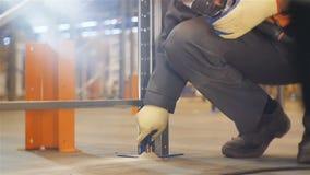 El trabajador de la cámara lenta pone la cerradura del metal en la construcción metrajes
