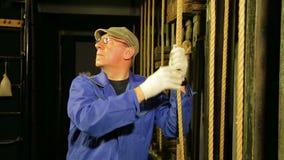 El trabajador de la etapa en guantes baja el cable del mecanismo de elevación de la cortina del teatro y lo sujeta metrajes