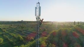 El trabajador de la mucha altitud en torre de comunicación de la antena hace una llamada móvil y muestra el pulgar para arriba en almacen de metraje de vídeo