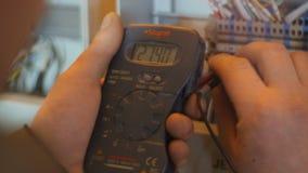 El trabajador de la opinión de la parte trasera comprueba la centralita telefónica con el metro de Digitaces almacen de metraje de vídeo