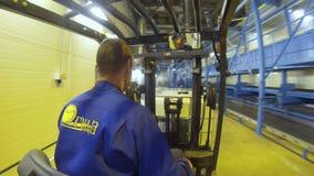 El trabajador de la opinión de la parte trasera en la carretilla elevadora toma el cubo y transportes almacen de video