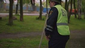 El trabajador de la policía de tráfico batido y cansa caminar a través de parque de la ciudad almacen de metraje de vídeo