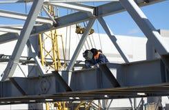 El trabajador de la soldadura eléctrica suelda con autógena construcciones metálicas Imágenes de archivo libres de regalías