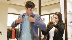 El trabajador de la tienda ayuda al cliente a intentar encendido la chaqueta en alameda