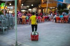 El trabajador de la zona de restaurantes arrastra una tina de platos sucios fotos de archivo